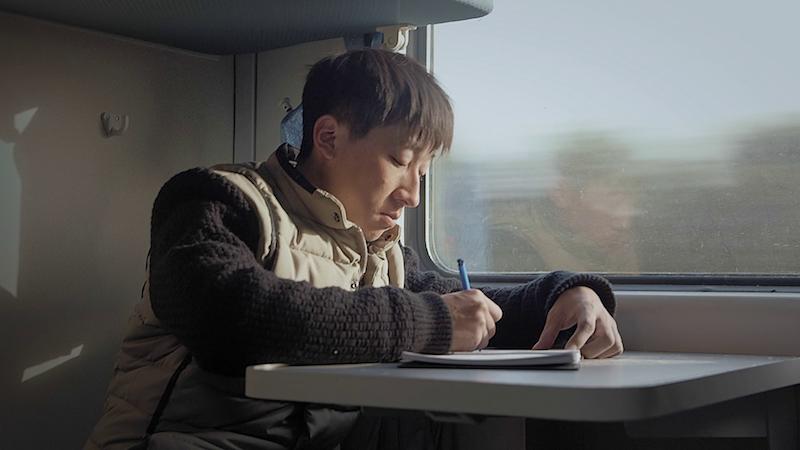 彝族充绒工吉克阿优在返回故乡的火车上 剧照|©️大象纪录
